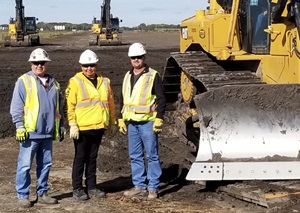 Three construction workers beside a backhoe