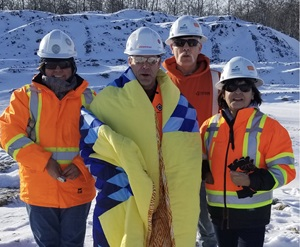 Four construction workers in winter one wearing a star blanket